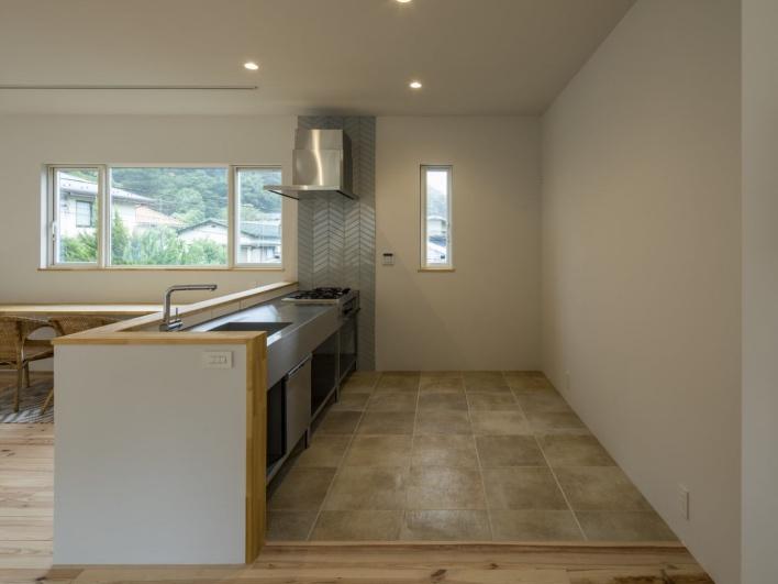 キッチンはステレンレスでクールな印象。収納棚を置いても余裕のスペースを確保。