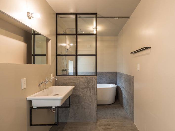 【施工事例】葉山T邸。海の帰りにそのまま直行できる1階奥のパウダールームと浴室も、モールテックスで仕上げた。扉のないセミクローズの浴室は、鉄の格子窓と相まって、海外のバスルームのような洗練を感じさせる。