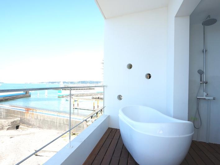 室内に浴室はない。あるのはバルコニーにバスタブとシャワーだけ。人目が気になる方のためにロールカーテンを設置してます。