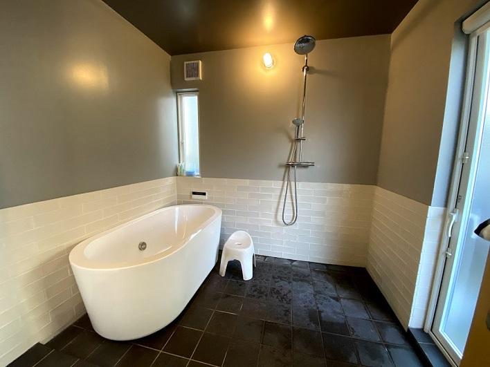 グレイッシュなトーンでまとめられた広いバスルーム。裏庭から直接アクセスできます。海遊び帰りに便利!