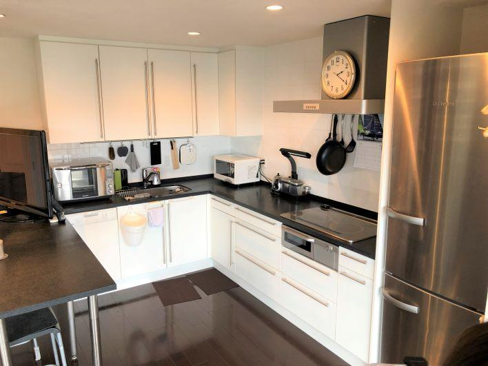 白い扉と天板のブラックがモダンなL字のキッチン
