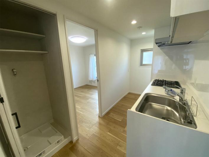 洗濯機置き場はキッチンの後ろ。扉がついているので生活感でなくていい。ナイス。